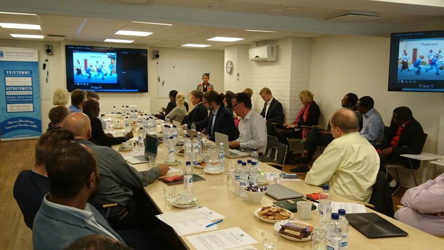 Kuva Finnish-Somali Business Council -kokouksesta, ihmiset istuvat pitkän pöydän ääressä ja katsovat diaesitystä