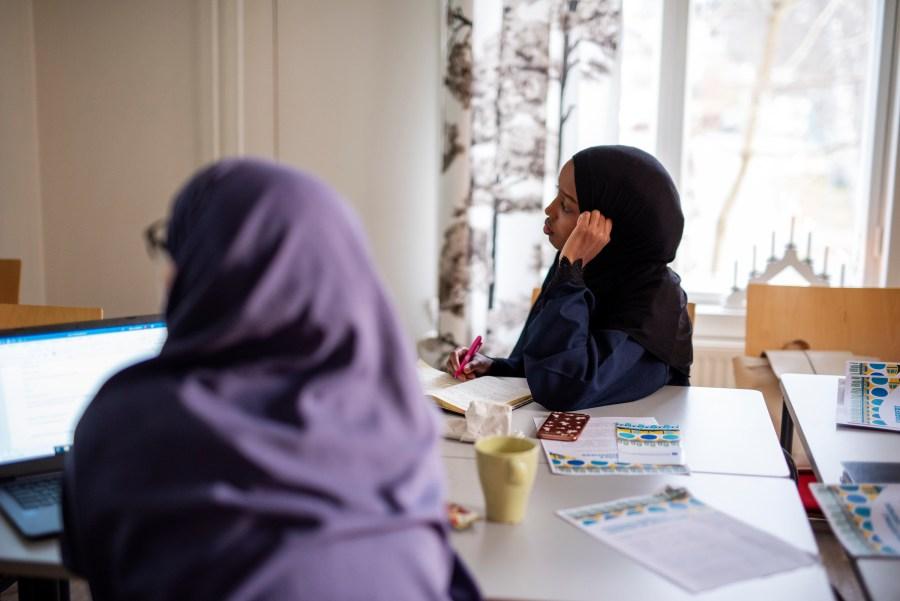 Kaksi naista istuu ja kuuntelee luentoa pöydän ääressä koulutuspäivänä