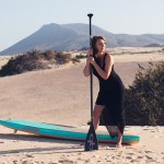 Girl standing with a SUP board and a paddle in her hand