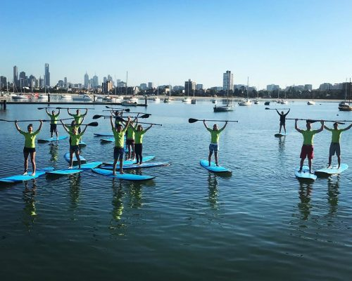 group of paddlers during a paddle boarding group lesson with Melbourne view