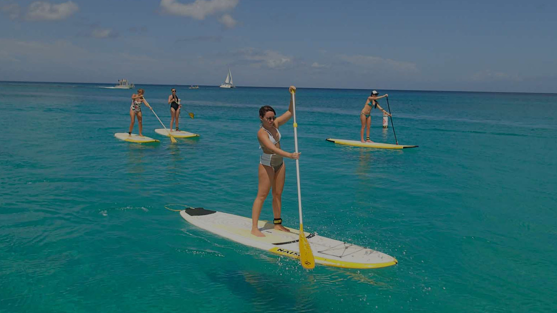 4 paddlers standing on a board in a clear water