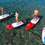 4 paddlers standing up on paddle board looking up toward a drone