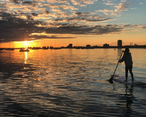 Girl stand up paddle boarding with sunset on St kilda beach after hiring paddle board