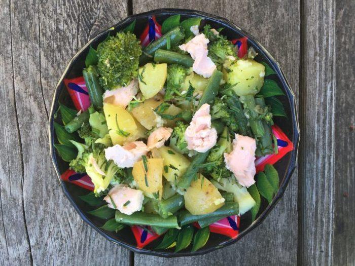 Manger du saumon avec des légumes verts