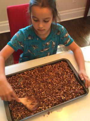 Louison étale les céréales sur la plaque de cuisson pour Super Boîte à Lunch