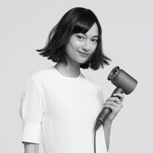 An Asian female model holding the Dyson Supersonic hairdryer with the new gentle air dryer attachment.