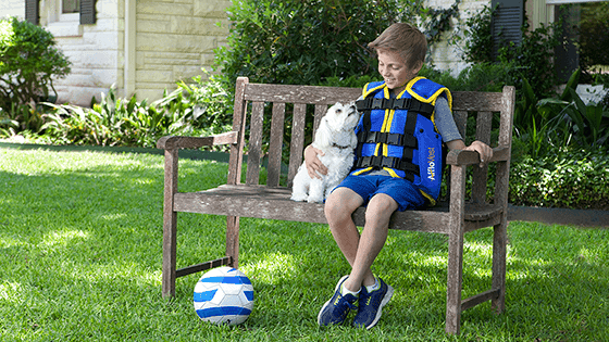 Boy with ventilator playing with dog