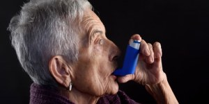 Elderly woman using inhaler