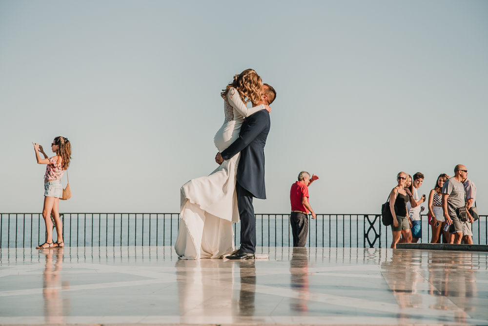 Novio cogiendo en brazos a su pareja y besándola en el balcón de España, fotografía de postboda en Nerja , Supercastizo