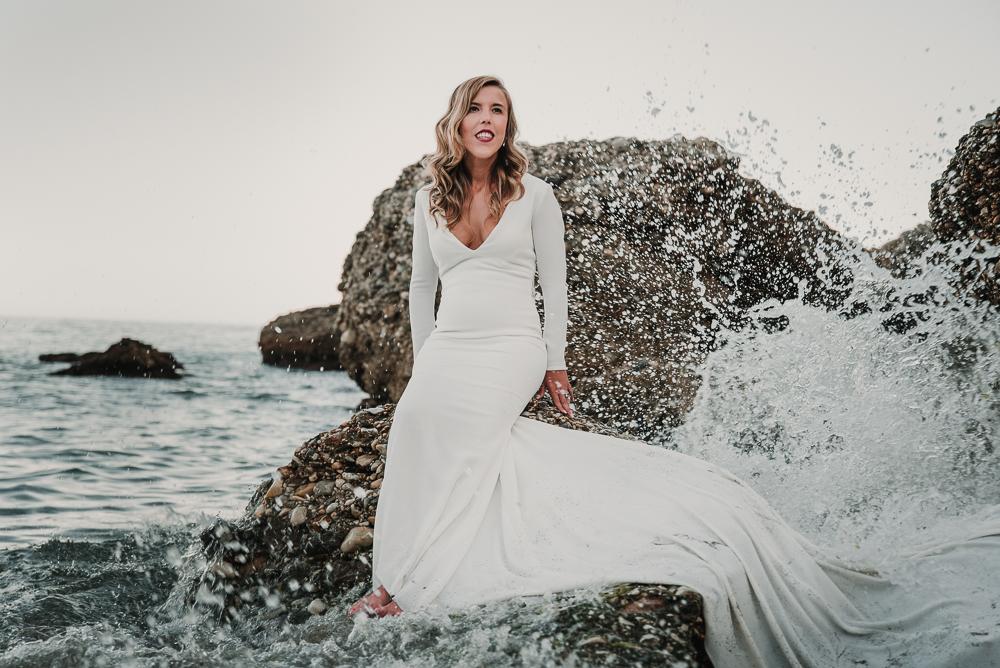 Novia sentada en una roca mientras las olas le salpican, fotografía de postboda en Nerja , Supercastizo