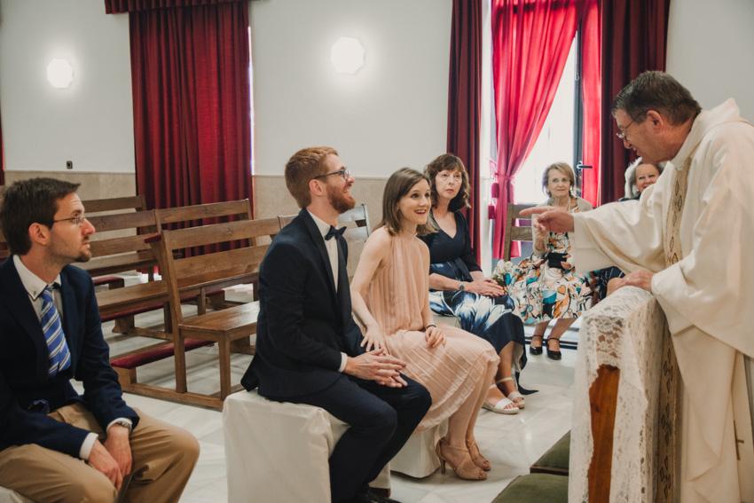 sacerdote bromeando con los novios