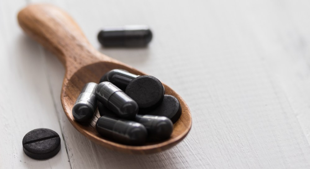 Activated charcoal pills in a spoon on white wooden background