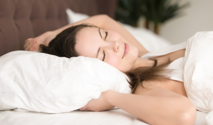 Pretty young woman enjoys long sleep in bed