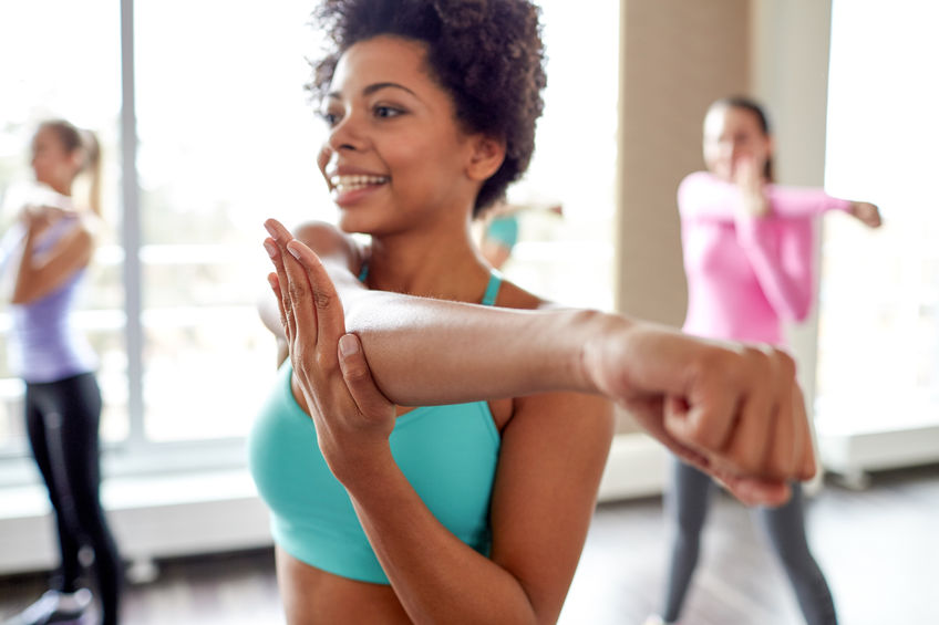 Photo of a woman doing a yoga stretch, with two other women also stretching in the background.