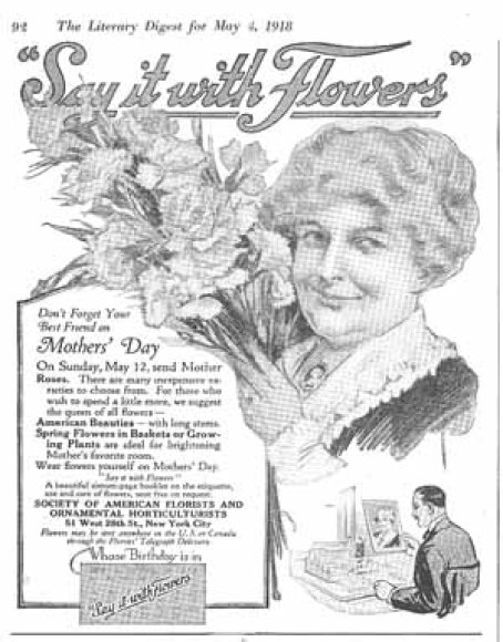 "Vintage, black-and-white magazine ad with a smiling woman holding a bouquet, with headline above in cursive that says, ""Say it with Flowers."" Above the headline is descriptive text that says ""The Literary Digest for May 4, 1918."" Below the woman in the ad, in the bottom right corner, a man is depicted holding a photo of the woman and smiling."