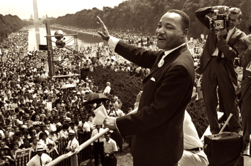 Photo of the Rev. Dr. Martin Luther King Jr. giving a speech to tens of thousands of people on the Washington Mall. He is standing, right arm outstretched, smiling.