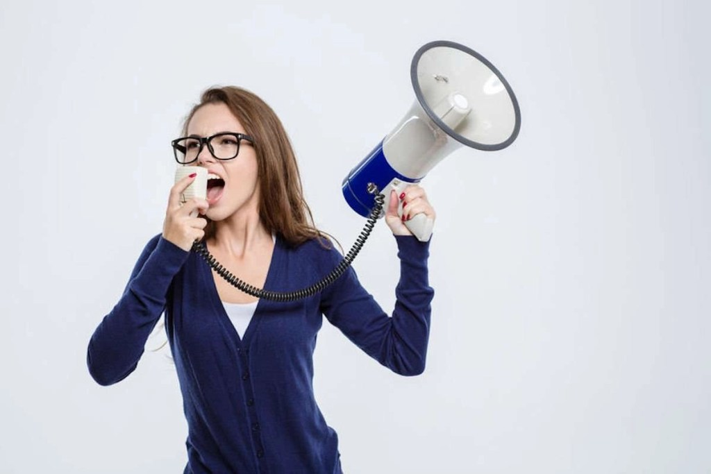 Photo of a young woman screaming into a megaphone isolated on a white background.