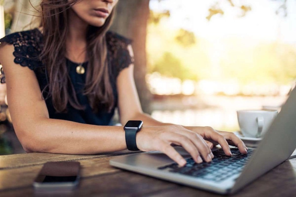 Photo of a young woman wearing a smartwatch using a laptop computer; it looks like she is at an outdoor cafe, and there is a coffee cup on the table too.