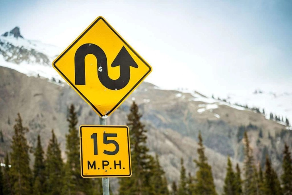 """Photo of a mountain scene with a focus on a road sign with a very curvy arrow and a """"15 MPH"""" speed limit posted."""
