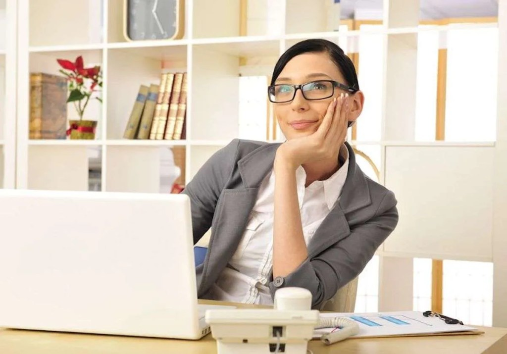 Photo of a woman in an office environment at her desk, starting off into space with a grin. She is deep in thought.