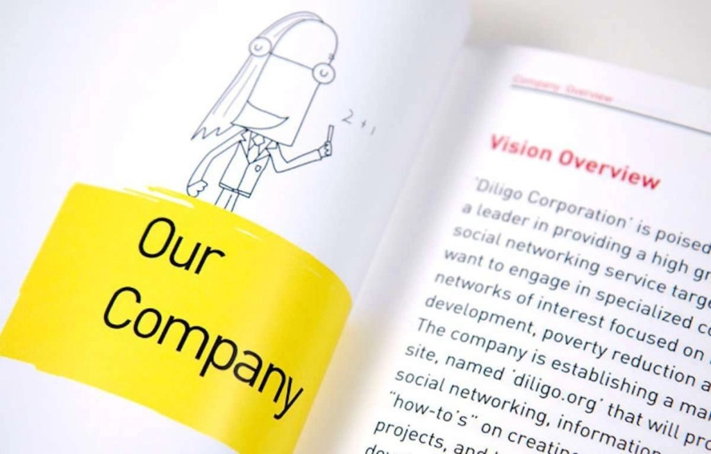 """Close-up photo of a sleek brochure; on one side is a cute little illustration of a person with a yellow block of text underneath that says """"Our Company,"""" and on the right is a page of text that starts out saying """"Vision Overview"""" in a red heading. It's obviously a marketing brochure for a generic company of some kind."""
