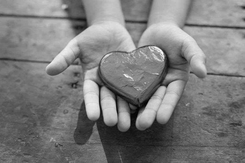 Black and white photo of a child's small hands holding a heart-shaped object, maybe a foil-covered heart-shaped chocolate.