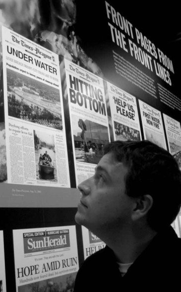 Photo of Dave Baker looking at an exhibit of newspaper front pages at the Newseum, 2010.
