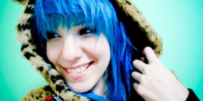 Mujer con el pelo azul, sonriendo, segura de sí misma
