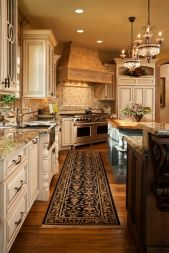 Warm elegant residential kitchen designed with high end finishes including hard wood floors, granite counter tops, custom cabinets, two islands, elegant chandaliers, large stove hood, and two stainless steel ovens.