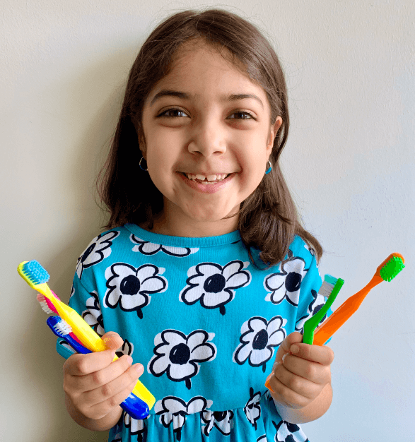 a smiling girl holds up colorful toothbrushes