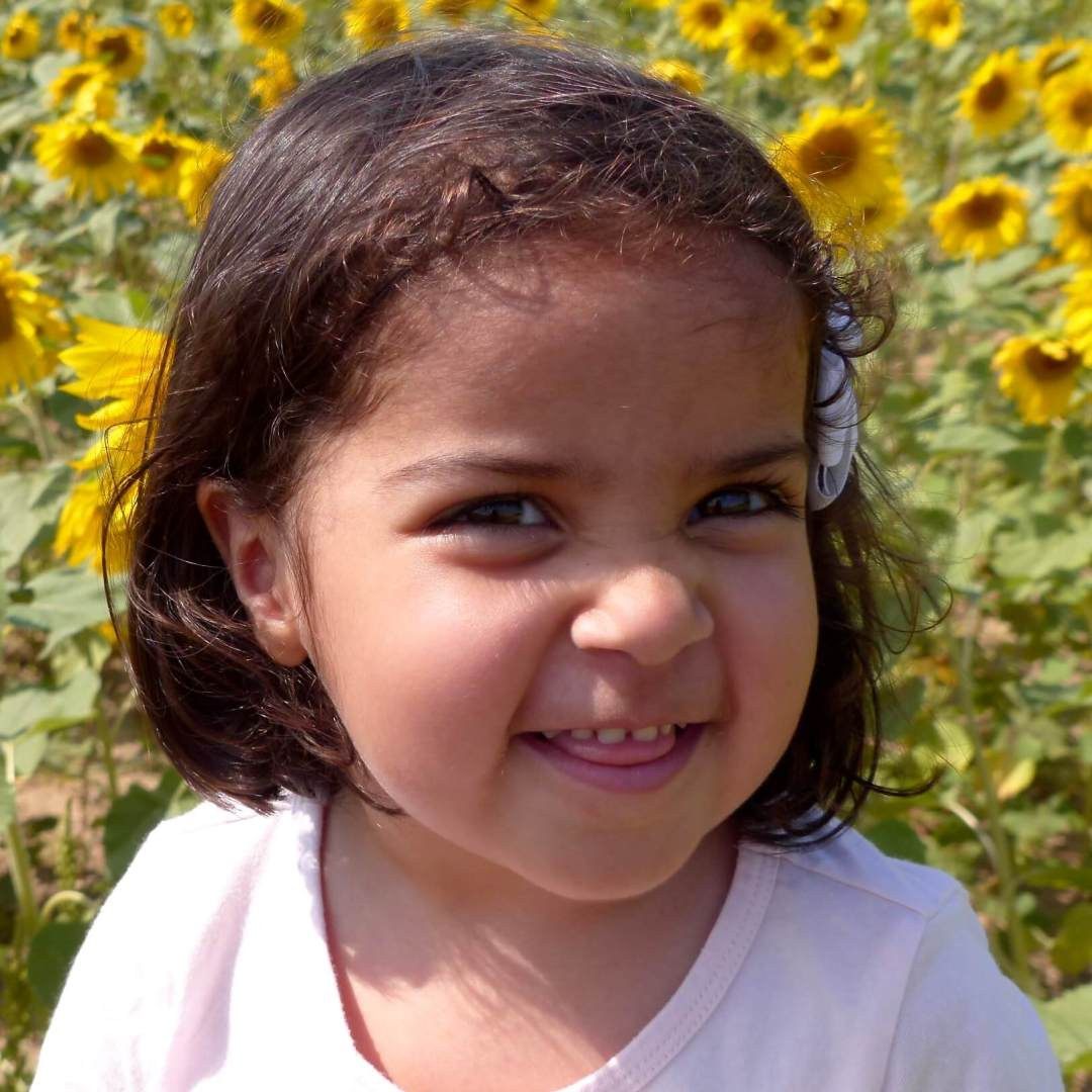 A toddler sits amid sunflowers. In a child her age, small cavities can grow quickly.