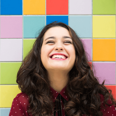A young woman smiles in front of a colorful tiled background
