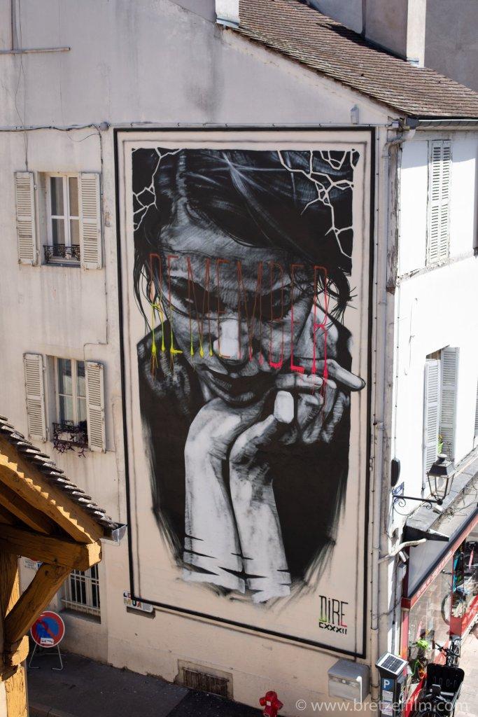 Fresque représentant une femme regardant au sol avec les mains croisés