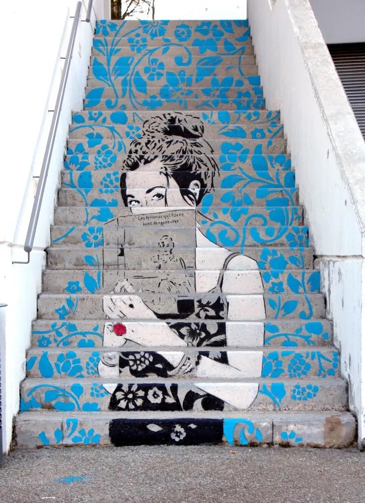 """L'œuvre """"Les femmes qui lisent sont dangereuses"""", créé en 2016 par Don Mateo. Se trouvant sur un escalier de la médiathèque de Francheville, il met en scène une femme mystérieuse avec un livre dans ses mains"""