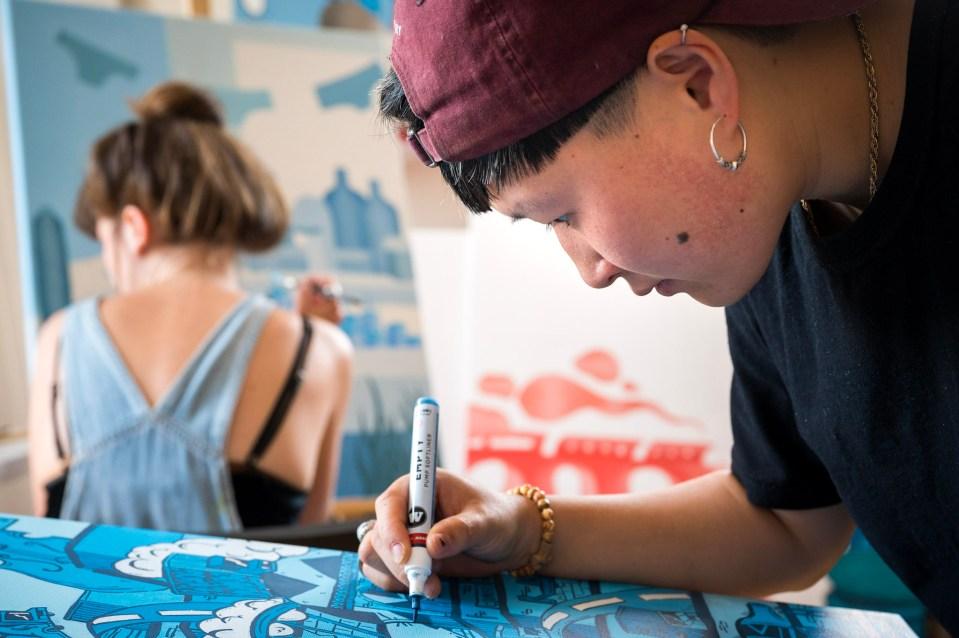 La street artiste Bouda qui dessine sur une toile pour son exposition.