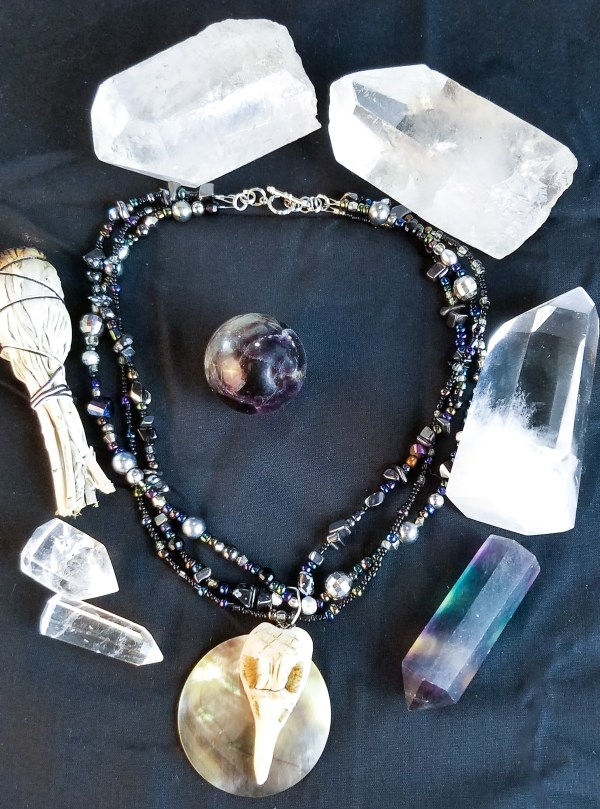 The Morrigan's necklace: Sculpted crow skull on shell beaded with hematite and obsidian