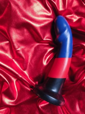BS Max Poly Pride striped silicone dildo on red metallic fabric bacground