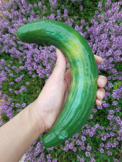 [Image: Self Delve curved cucumber dildo among purple sage flowers]
