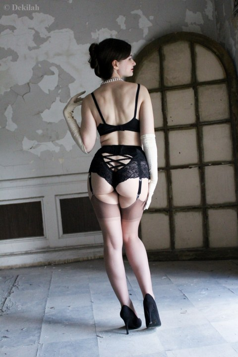 [Image: Dekilah modeling black lingerie and heels]
