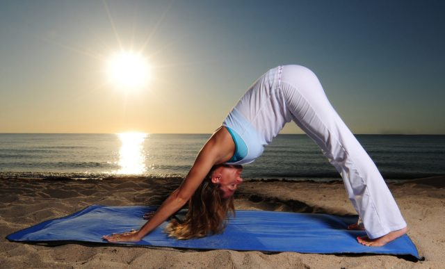 Downwards Facing Dog Pose on the beach. Flexibility and Core Training. Balance.