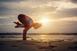 Woman practicing Bakasana Yoga Asana outdoors. Flexibility and Core Training. Balance.