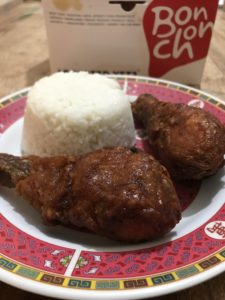 BonChon drumsticks, spicy foreground, soy-garlic background with rice.