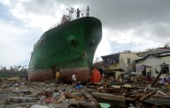 People walk among debris next to a ship washed ashore in the aftermath of Typhoon Haiyan at Anibong in Tacloban, the Philippines on Nov. 11, 2013. Photo: Noel Celis/AFP/Getty Images.