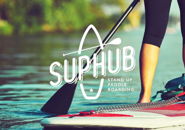 A woman stand up paddleboarding on a river with SUPHubNI logo