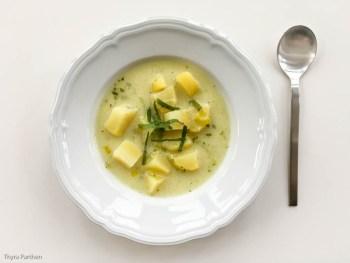 Kartoffelsuppe mit Sauerampfer und Buttermilch in weißen Teller angerichtet - von oben