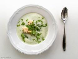 Spargelsuppe mit Kerbel und Lachswürfeln von oben aufgenommen in weißem Teller mit Löffel