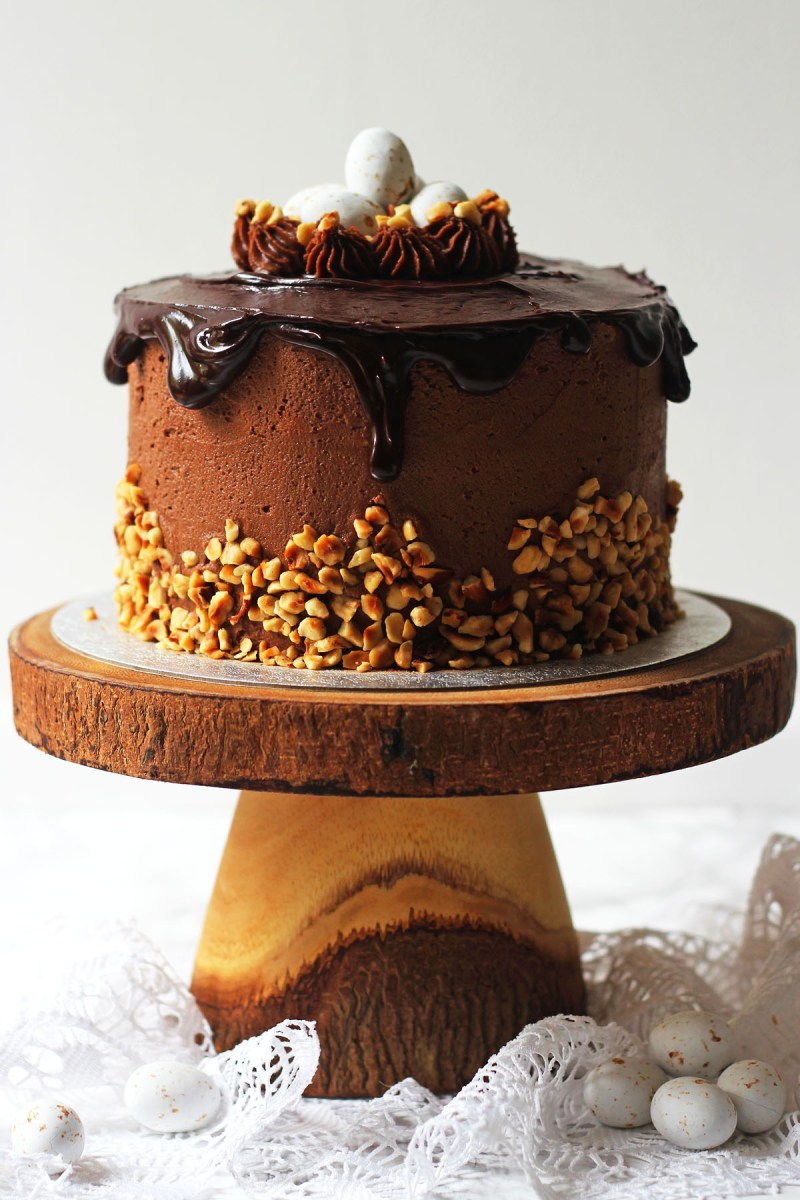 Nothing says Easter like a vanilla sponge cake smothered in Nutella buttercream, chopped hazelnuts, dark chocolate ganache, topped with praline Easter eggs! Get the recipe for this Praline Easter Cake at Supper in the Suburbs!