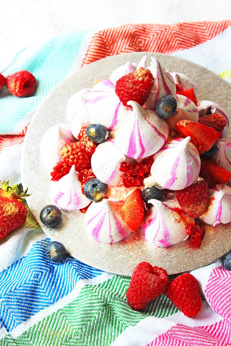Eton Mess Stack made with meringue kisses, raspberries, strawberries, blueberries and whipped cream. Get the recipe at Supper in the Suburbs!