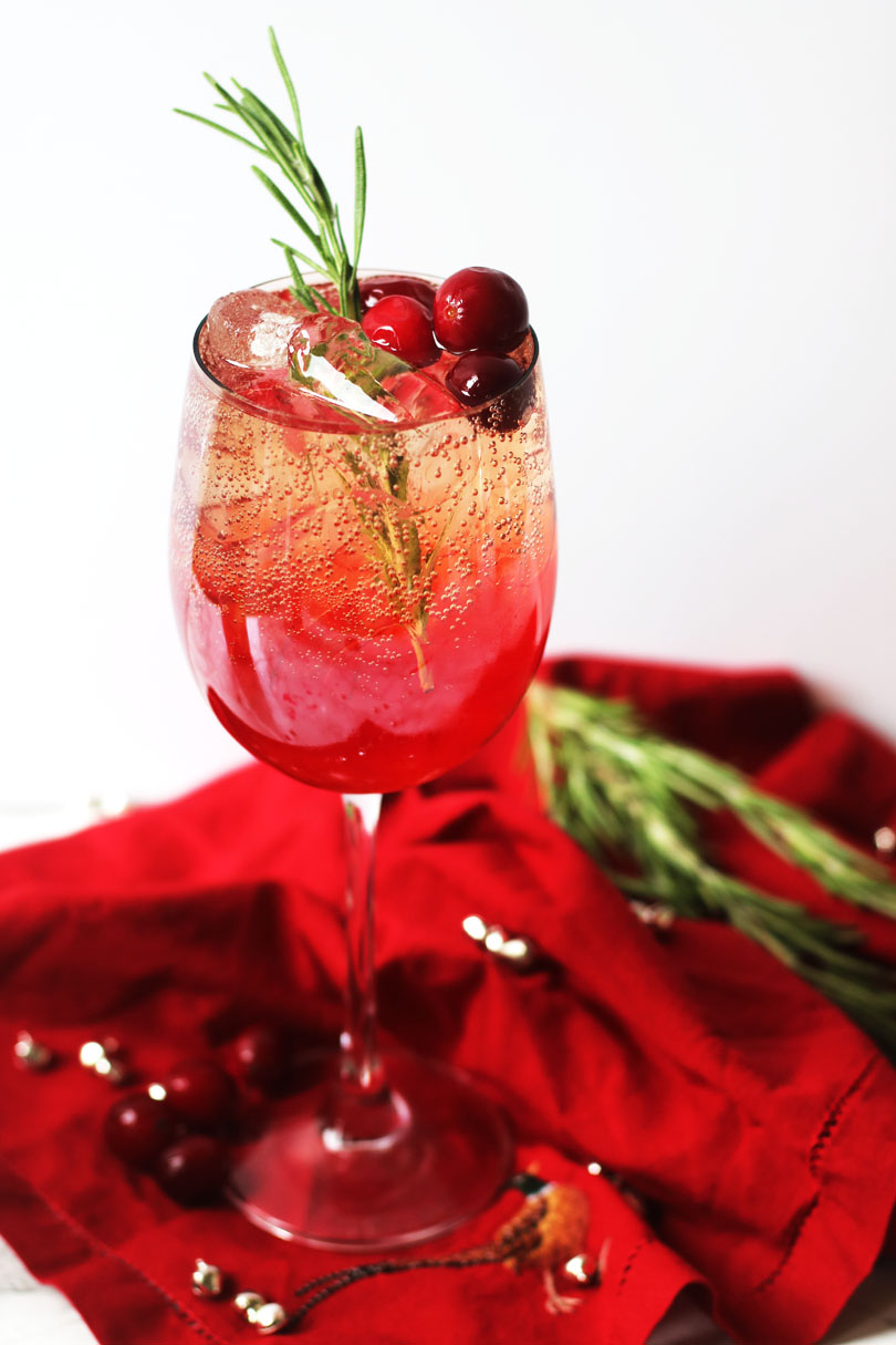 Cranberry and Aperol Spritz, a single wine glass of Christmas cocktail, garnished with fresh cranberries, rosemary and served over ice.