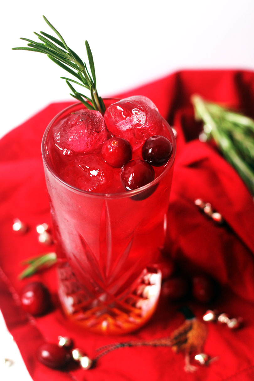 A long cocktail and cranberry juice and amaretto, garnished with fresh cranberries and rosemary